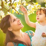 Happy Woman And Child In The Blooming Spring Garden.child Kissin